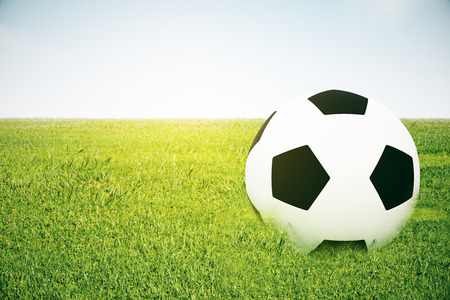 Closeup of football on grass. Grey background. 3D Rendering