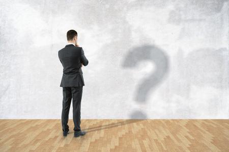 Uomo d'affari premuroso con il punto interrogativo ombra in camera con muro di cemento e pavimento in legno Archivio Fotografico