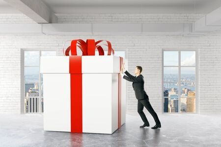 pushing: Businessman pushing huge present box in brick interior with city view. 3D Rendering