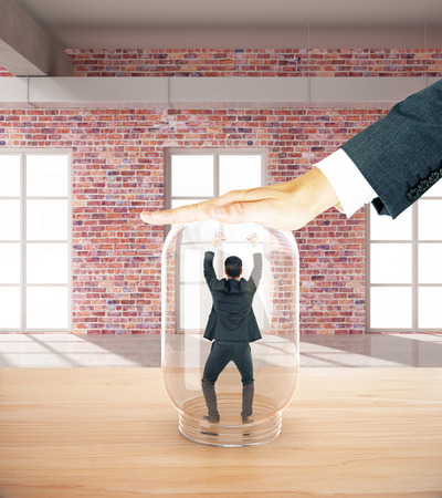suffocating: Employee miniature trapped inside transparent glass jar by employers hand. Red brick interior background