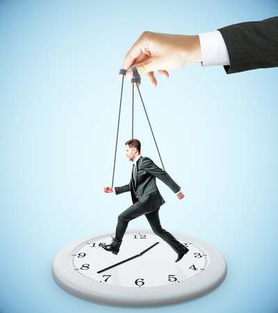 puppet master: Huge hand making businessman run on abstract clock. Light blue background. Manipulation and control concept Stock Photo