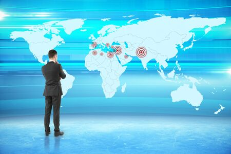 geo: Thoughtful businessman looking at map with targets on abstract blue background. Geo targeting concept. 3D Rendering Stock Photo