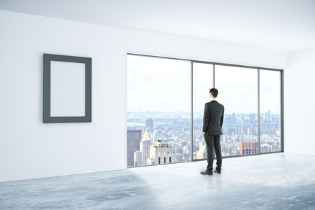 looking at view: Businessman looking out of window in concrete interior with blank picture frame and city view. Mock up, 3D Rendering