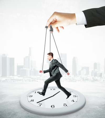 puppet master: Huge hand making businessman run on abstract clock. Abstract city background. Manipulation and control concept Stock Photo