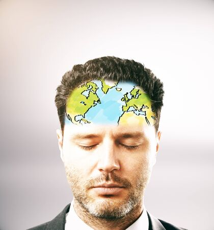 Portrait of pensive businessman with map on forehead. Light background Stock Photo