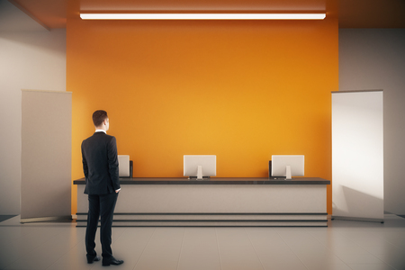 standing reception: Thoughtful businessman standing in orange interior with blank poster, empty wall and reception desk. Mock up, 3D Rendering Stock Photo