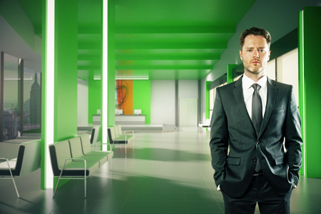 standing reception: Confident businessman with hands in pockets standing in green lobby interior with reception desk and New York city view