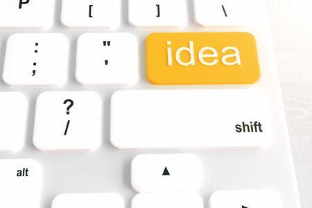 leadership key: Closeup of white keyboard with orange idea button on light desktop. 3D Rendering Stock Photo