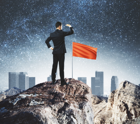 Leadership concept with businessman on mountain top with red flag looking into the distance on city background