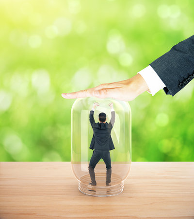 employers: Employee miniature trapped inside transparent glass jar by employers hand. Abstract green background