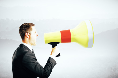 businessman using a megaphone: Side view of emotinal businessman screaming into megaphone on abstract grey background. Communication concept Stock Photo