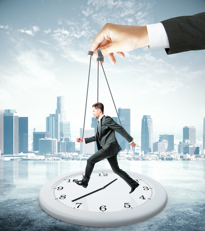 puppet master: Huge hand making employee run on abstract clock. City background. Manipulation and control concept Stock Photo