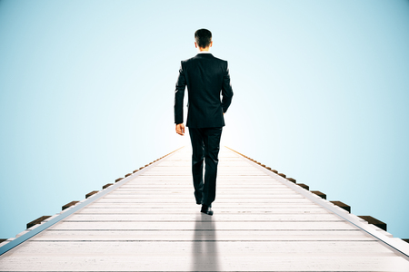 businessman suit: Businessman walking on wooden pier. Blue background with abstract sunlight. Success concept