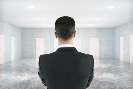 many doors: Close up of thoughtful businessman standing in concrete room with many white doors. Success concept