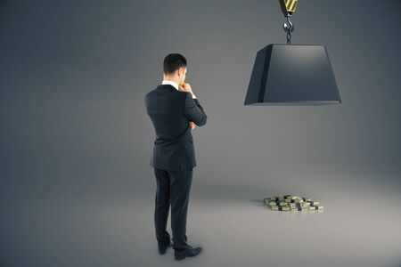 heavy risk: Man looking at heavy block on hook above cash pile on grey background. Risk concept. 3D Rendering