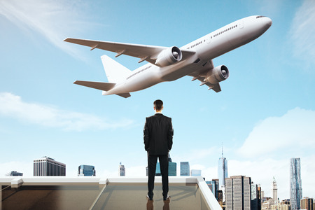 air travel: Travel concept with businessman on roof looking at flying by airplane on city background Stock Photo