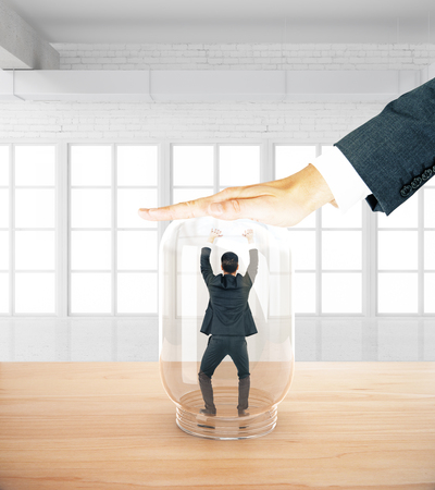 employers: Stressed businessman miniature trapped inside transparent glass jar by employers hand. White interior background