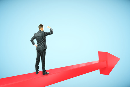 expanse: Success concept with businessman standing on red chart arrow and looking intor the distance on blue background