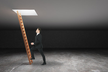 leading light: Businessman climbing wooden ladder in dark grey basement leading out to light. Freedom concept. 3D Rendering