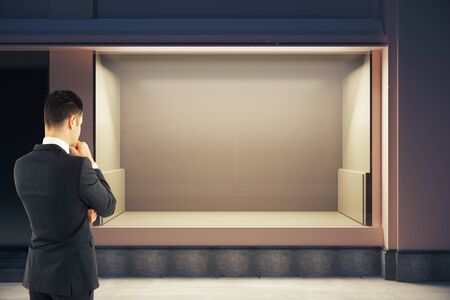 men back: Thoughtful businessman looking at empty clean storefront at night. Mock up, 3D Rendering Stock Photo