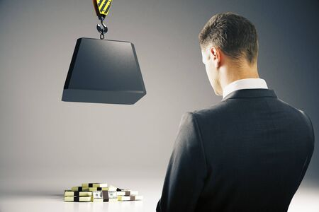 heavy risk: Businessperson looking at heavy block on hook above cash pile on grey background. Risk concept. 3D Rendering