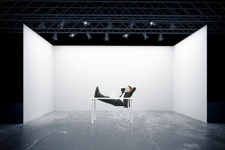 trussing: Relaxing businessman with feet on table against truss stage. 3D Rendering