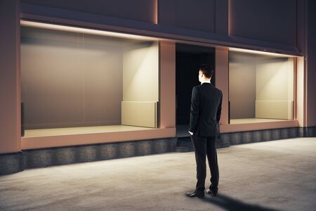 storefront: Confident businessman looking at empty clean storefront at night. Side view, Mock up, 3D Rendering
