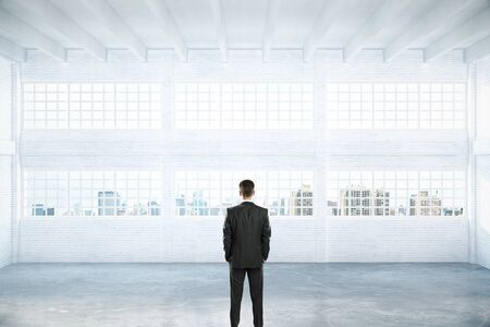 daylight: Businessman standing in empty light hangar interior with daylight and city view. 3D Rendering Stock Photo