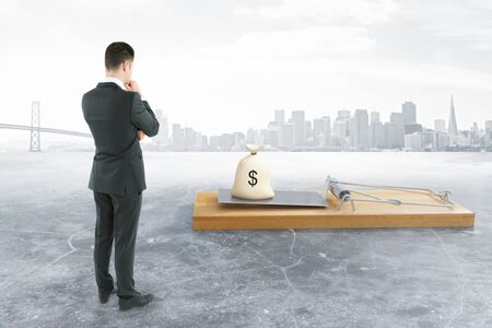 Businessperson looking at abstract mousetrap with money sack on grey city background. Risk concept. 3D Rendering