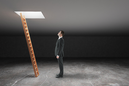 leading light: Businessman looking at wooden ladder in dark grey basement leading out to light. Freedom concept. 3D Rendering Stock Photo
