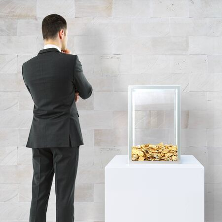 Thoughtful businessperson looking at donation box with golden coins on concrete tile background. 3D Rendering