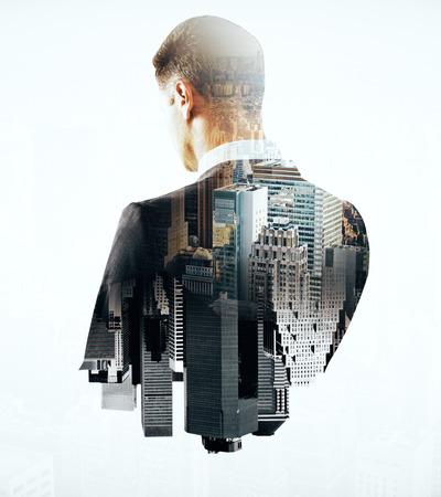 Achter mening van nadenkende zakenman en de stad op lichte achtergrond. Double exposure