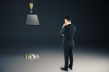heavy risk: Businessman looking at heavy block on hook above cash pile on grey background. Risk concept. 3D Rendering