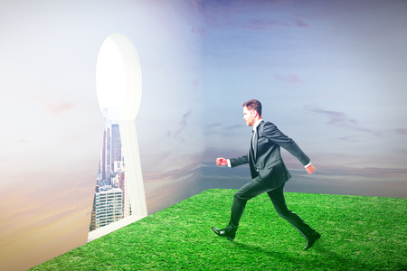 towards: Businessman in field running towards abstract keyhole opening leading to city. Escape concept