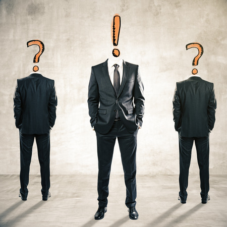 indecisive: Two question mark headed businessmen behind exclamation mark headed man on textured concrete background. Leadership and management concept Stock Photo