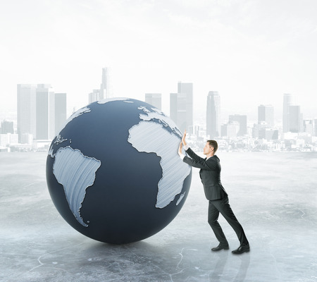 globe  the terrestrial ball: Businessman pushing abstract terrestrial globe on city background. Global business concept. 3D Rendering