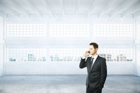 hangar: Businessman talking on phone in empty light hangar interior with daylight and city view. 3D Rendering