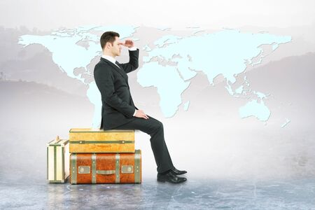 sitting on the ground: Businessman sitting on suitcases and looking into the distance on landscape background with abstract map. Business trip and research concept