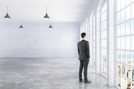 Businessman standing in white brick and concrete interior with ceiling lamps and window with city view. 3D Rendering