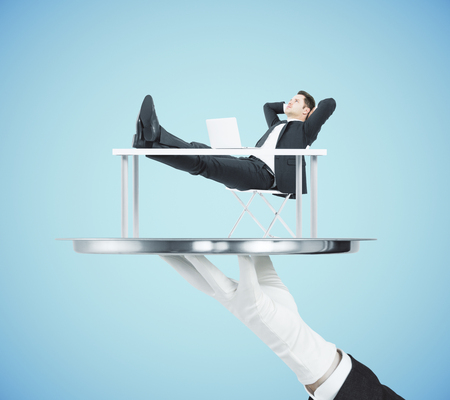 Hand in glove holding abstract silver tray with relaxing businessman on blue background