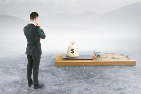Businessman looking at abstract mousetrap with money sack on foggy background. Risk concept. 3D Rendering