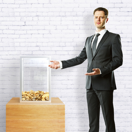 Young businessman in suit showing donation box on white brick background. 3D Rendering