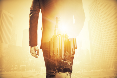 Back view of businessman in suit walking on abstract city background with sunlight. Double exposure