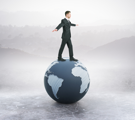 Young businessman in suit balancing on abstract globe. Landscape background. 3D Rendering Reklamní fotografie