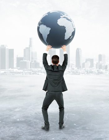 sphere standing: Back view of young businessman holding terrestrial globe on abstract city background. 3D Rendering. International business concept