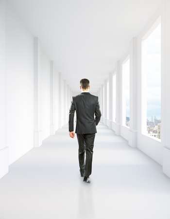 corridor: Walking businessman in concrete corridor interior with city view. 3D Rendering Stock Photo