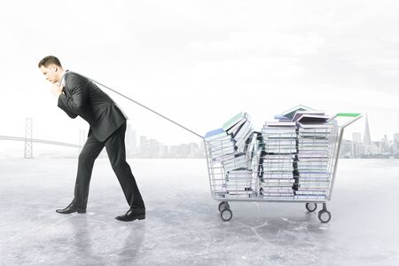 dragging: Businessman dragging trolley with heap of books on white background. Education concept. 3D Rendering Stock Photo