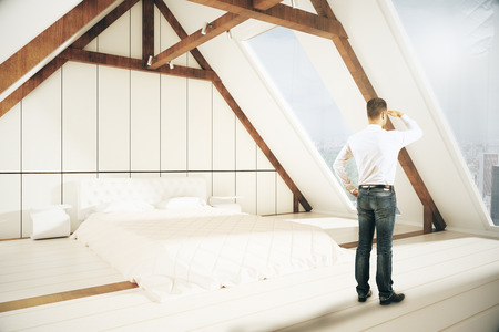 loft interior: Young man looking into the distnace in loft bedroom interior. Research concept. 3D Rendering Stock Photo
