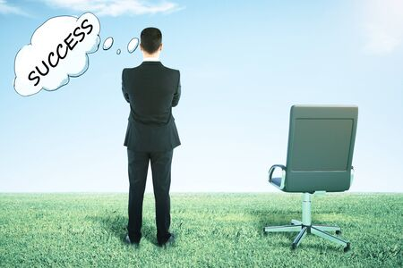 Back view of swivel chair and businessman on grass looking into the distance and thinking about success Stock Photo