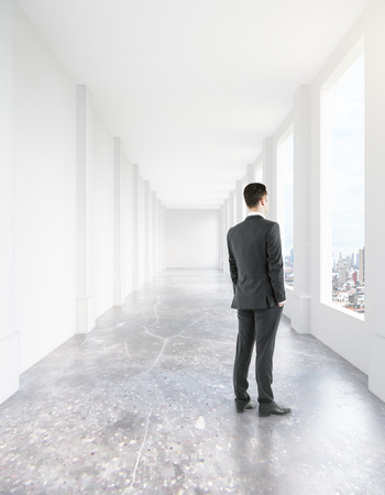 looking straight: Businessman looking out of window in concrete corridor interior with city view. 3D Rendering